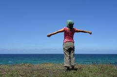Happy woman with arms wide open at the coast Stock Photos
