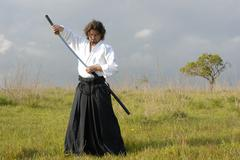 young aikido man with a sword, outdoors - stock photo
