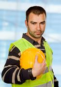 proud worker standing looking at the camera - stock photo