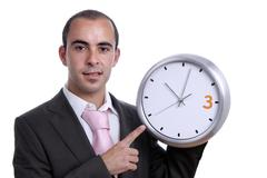 handsome business man holding a clock - stock photo