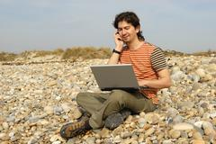 young casual man with laptop at the beach - stock photo