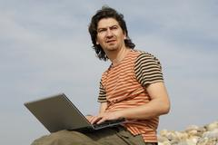 Young casual man with laptop at the beach Stock Photos