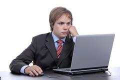 young bored business man working with is laptop - stock photo