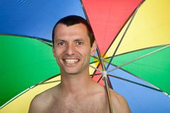 Young happy man with umbrella, studio picture Stock Photos