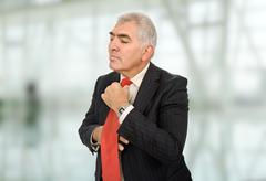 Business man adjusting his tie at the office Stock Photos