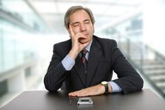 mature business man on a desk, sleeping, at the office - stock photo