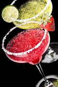 One classic and a strawberry margarita in front of a black background Stock Photos