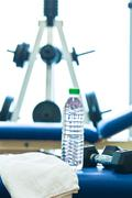 Weights stand, bench of a gym with towel and water bottle Stock Photos