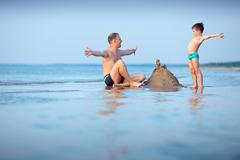 Young father and his son having fun at beach Stock Photos
