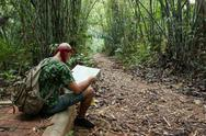 Stock Photo of travelling man sitting and looking at the map in the bamboo forest