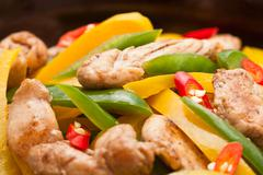 fried chicken with capsicum on red table cloth - stock photo