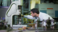 Young male machine operator working in a factory Stock Footage
