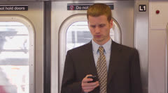 Man Using Smartphone in Subway - Above Ground Stock Footage