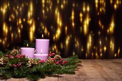 Three candles in an advent flower arrangement Stock Photos