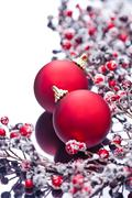 Two christmas baubles and holly berries Stock Photos