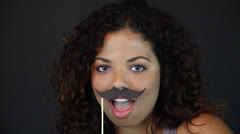A young Feminine holds funny Moustache in Face with various expressions Stock Footage