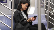 Stock Video Footage of Woman Viewing Cell Phone on Clean Subway