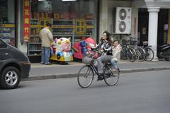 Stock Photo of mother with her smiling daughter riding bicycle in shanghai
