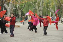 SEnior Chinese dancing with red fans - stock photo