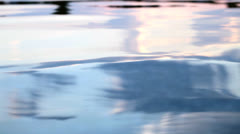 From dusk colored water surface in motion by gentle waves - stock footage