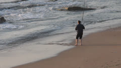 Fisherman with fishing  spinning rod on the beach Stock Footage
