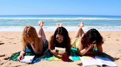 Pretty girls reading books on the beach Stock Footage
