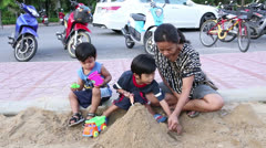Asian Mother Playing In The Sand Box With Her Two Sons Stock Footage