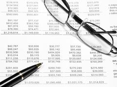 Business financial chart analysis with pen & eyeglasses Stock Photos