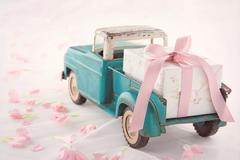 Antique toy truck carrying a gift box with pink ribbon Stock Photos