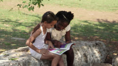 Young people and education, two little girls reading book in city park - stock footage
