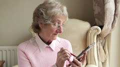 Senior woman sending text or email using tablet at home Stock Footage