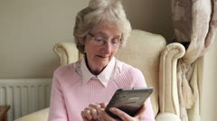 senior woman sending text or email using tablet at home - stock footage