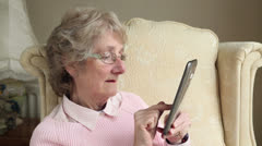 Elderly woman on the internet with a tablet at home Stock Footage