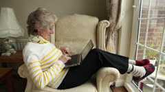 elderly woman sitting in chair using laptop at home - stock footage