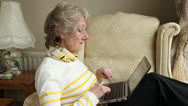 Stock Video Footage of elderly woman sitting in chair using laptop at home