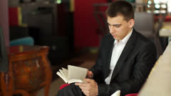 Liikemies lukee kirjaa ja hymyilee kahvila Arkistovideo