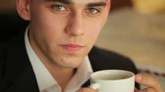 Young adult drinking coffee and smiling Stock Footage
