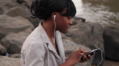 Woman Listening to Music on Rocky Shore Stock Footage