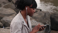 Stock Video Footage of Woman Listening to Music on Rocky Shore