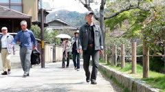 Japanese people walking on Path of Philosophy in Kyoto, Japan Stock Footage