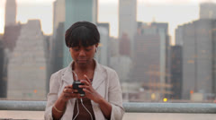 Woman Listening to Music in front of City Skyline Stock Footage