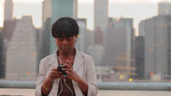 Stock Video Footage of Woman Listening to Music in front of City Skyline