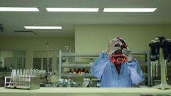 Biotech and pharmaceutical lab with researcher wearing mask, checking vaccine Stock Footage