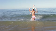 Father Carrying Daughter On Shoulders As They Run In Sea Stock Footage