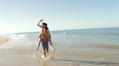 Man Giving Woman Piggyback As They Run Along Beach - stock footage