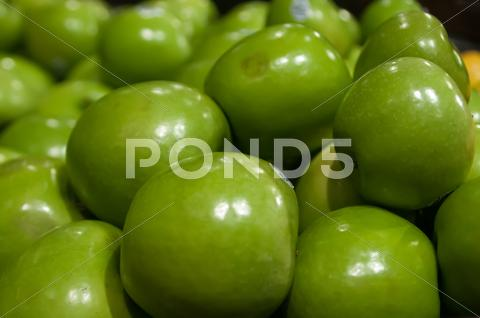 Stock photo of green apples on display at farmers market
