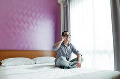 Happy man with cellphone in bedroom Stock Photos