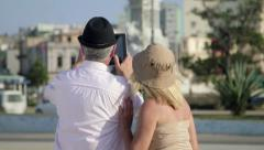 Travel and elderly man and woman, tourists looking at monument, taking picture Stock Footage