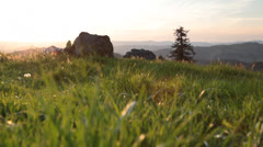 Crane shot of grassy field with view of rolling mountains - stock footage