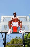 Stock Photo of basketball player sitting in hoop